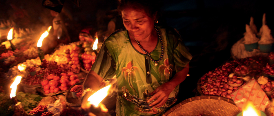 A seller in a traditional market on the island of Sumba prepares oil lamps at her stall as night falls. On the outer islands, electrical power is often unreliable or non-existent. Photo: Josh Estey