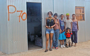 In transit: Ayesha, Nazley and their new neighbours outside Ayesha's home in the temporary relocation area.