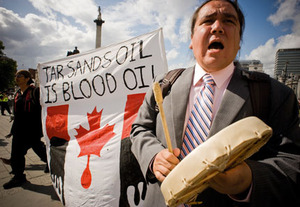 Canadian indigenous activist Clayton Thomas-Muller (right) leads the tar sands protest through London's Trafalgar Square with a traditional song. Lionel Lepine (left) carries the banner.