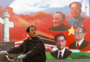 A man in Shanxi province rides past the communist dynasty of leaders (clockwise from top) Mao Zedong, Jiang Zemin, Hu Jintao and Deng Xiaoping.Shanghai Stringer / Reuters
