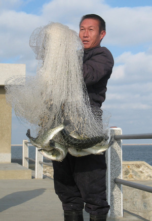 A farm labourer shows off his fine catch on a freezing winter day. Our group was later offered the fish for lunch, and given the rest to take back home.