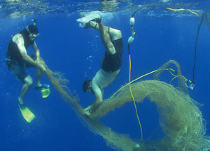 Two crew members attach a tracking buoy to a 'ghost net'. Hundreds of plastic nets are abandoned in the ocean causing widespread damage to the marine environment. The buoys have transmitters that allow the nets to be tracked by satellite. The Alguita has tagged six 'ghost nets' since 2005.