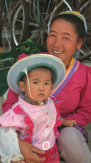 This young mother in Yunnan province seems happy to have a girl. Photo: Julio Etchart