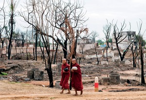 Sectarian divide: Buddhist monks walk through a devastated Muslim area in Meiktila.Photo: Brennan O'Connor