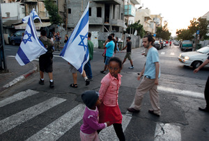 Children cross the street as residents of south Tel Aviv protest against African migrants from Eritrea, Sudan and South Sudan in their neighbourhoods, in May 2012. The week before, a similar protest led to a rampage that an Israeli broadcaster dubbed a 'pogrom'. Protests such as these still take place on a regular basis in Tel Aviv and other major cities in Israel.Baz Ratner/Reuters