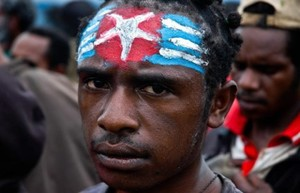 A protester in West Papua, face painted with the 'Morning Star' flag.