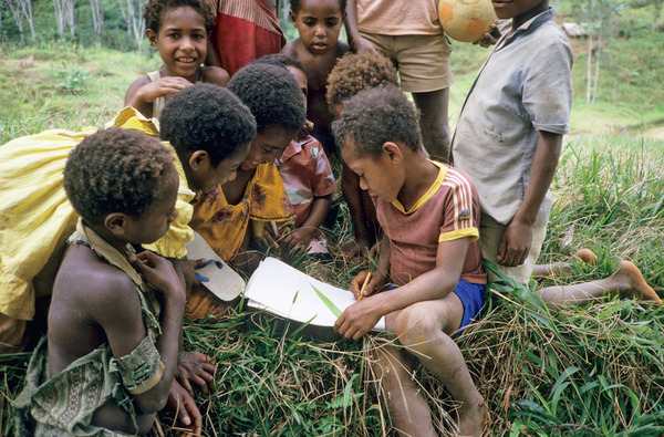 Aseki children reading in Papua New Guinea. With one language for every 8,300 inhabitants it is the most linguistically diverse country in the world.