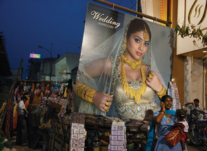 Dazzle or bust: a billboard model for a jewellery shop advertises the buckling-under-gold bridal look aimed for the status conscious, while the street market outside bustles with more humdrum wares, in Chennai, India.Randy Olson/©National Geographic Image Collection /Alamy