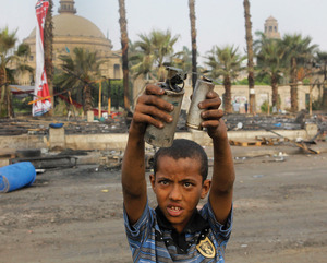 A child holds up an empty teargas canister in the ruins of a Cairo protest camp.