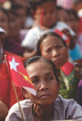 A woman listens to democracy leader Aung San Suu Kyi at a rally in Burma. But are recent reforms in the country due to foreign aid leverage?
