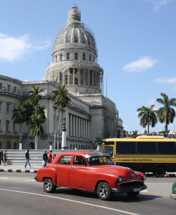 Behind the vintage taxi is one of Havana's new Japanese-made co-operative buses. And behind that – the city's iconic Capitolio, also being renovated.