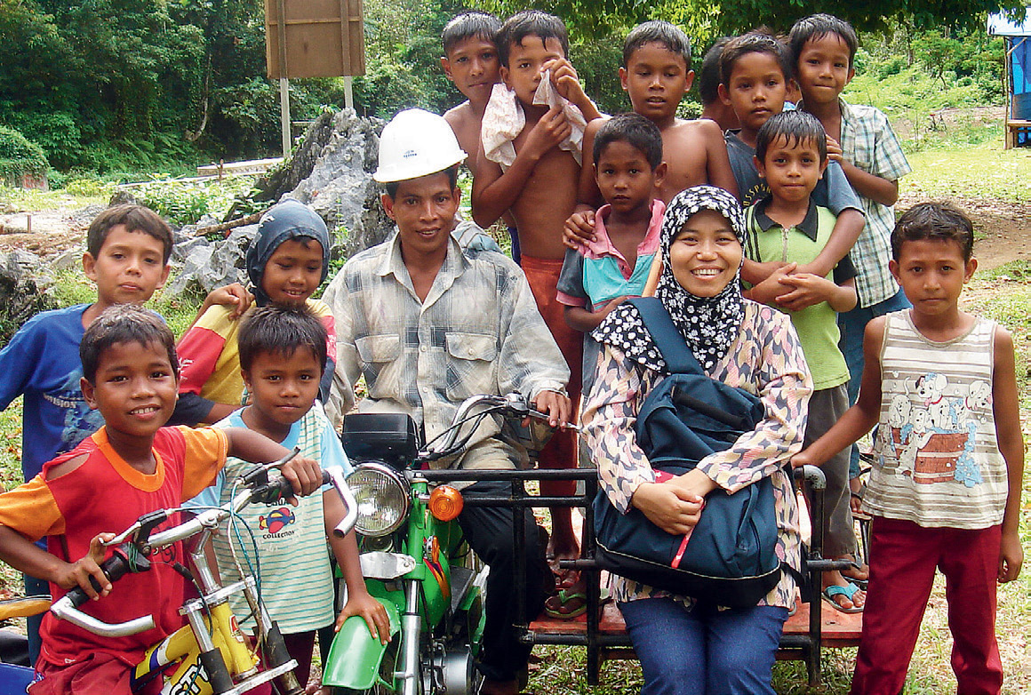 Going with the flow: Tri Mumpuni Iskandar (front row, second from right), from IBEKA with villagers at the launch of a microhydro project in Aceh, Indonesia.