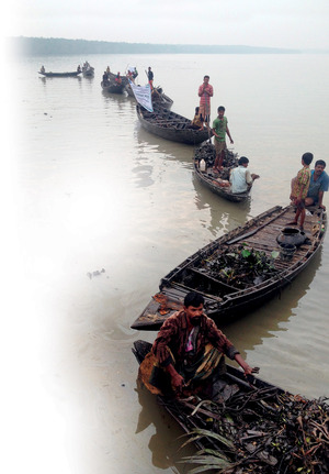 A hazardous catch: villagers gathering oil-smeared plants from the river.