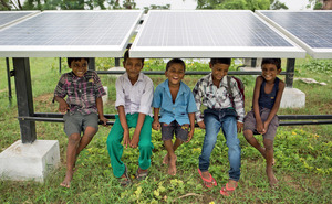 Under the sun: Children shelter beneath a solar panel in Dharnai village.Photo: Vivek M. / Greenpeace