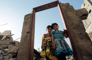 Three-year-old twin Palestinian girls pose in a doorway that's still standing after Israel's bombing campaign.EPA European Pressphoto Agency B.V. / Alamy