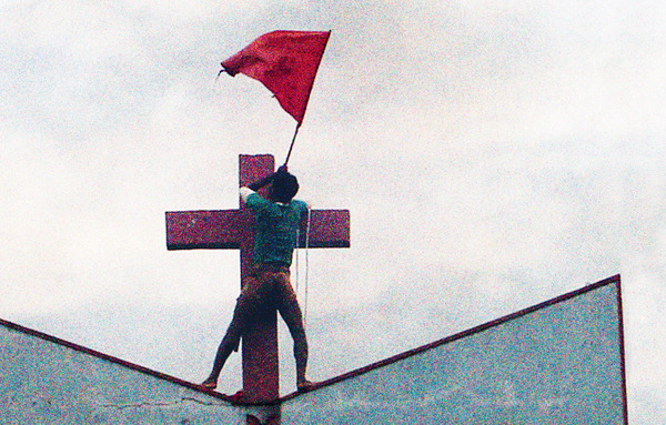 Contested territory: a Hindu nationalist raises a saffron flag atop a church in Muniguda in India's Orissa state. Minority communities in India are regularly targeted by politically instigated Hindu groups, and churches have been burned and defaced. Photo: AP/Press Association Images