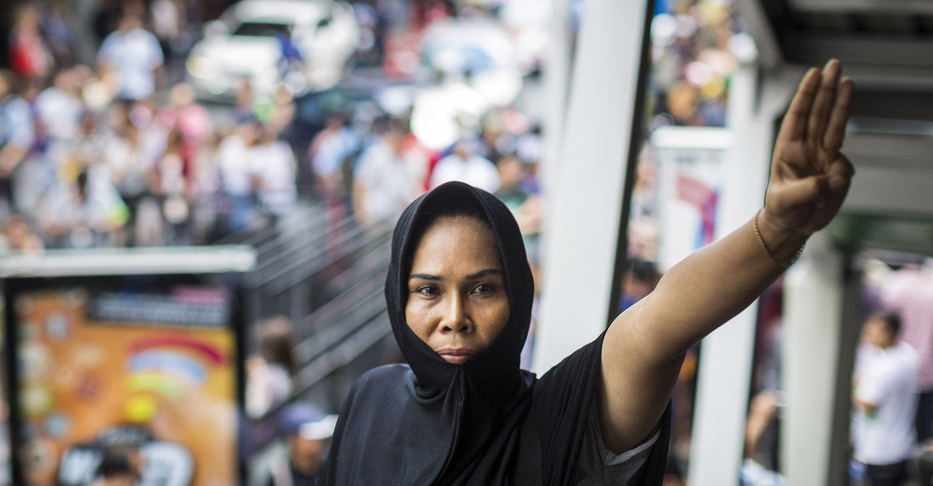 Farewell, democracy: using the Hunger Games' three-fingered salute, which represents thanks and goodbye to a loved one, a Thai woman marks the perceived end of democracy in her country.