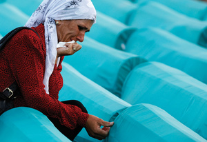 A Bosnian woman weeps over the remains of family members recovered from a mass grave, victims of the 1995 Srebrenica massacre.