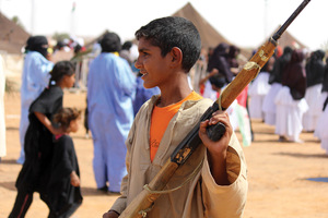 Carrying a gun to symbolise the independence war of 1975-91, a Saharawi boy takes part in an annual parade at a refugee camp in Algeria. He is part of a generation that has never seen its homeland.