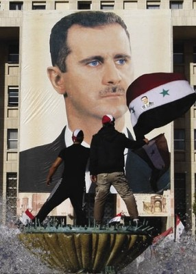 Watch you don't fall: supporters of President Bashar Assad stand atop a fountain during a rally in Damascus.Muzaffar Salman/AP Photo