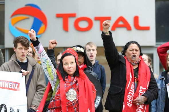 Jenni Laity, a Sámi women from Scandinavia, protesting in solidarity with other Indigenous people outside Total headquarters against tar sands and oil extraction.