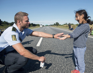 Mixed messages: refugees have received a varied reception as they journey through Europe. Here, a policeman plays with a girl last September in Denmark, a cut-through for many Syrian and Iraqi refugees heading for Sweden. Photo: Claus Fisker/Reuters