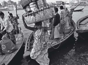 Carrying a large basket full of aluminium lunch containers called tiffins, a woman disembarks from a passenger boat over the river. She delivers dozens of tiffins across the river to office, garment and tannery workers in Dhaka city.