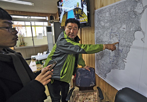 The mayor of Sinsan village points out a map of the proposed air city development on Jeju island, and its negative consequences for locals.