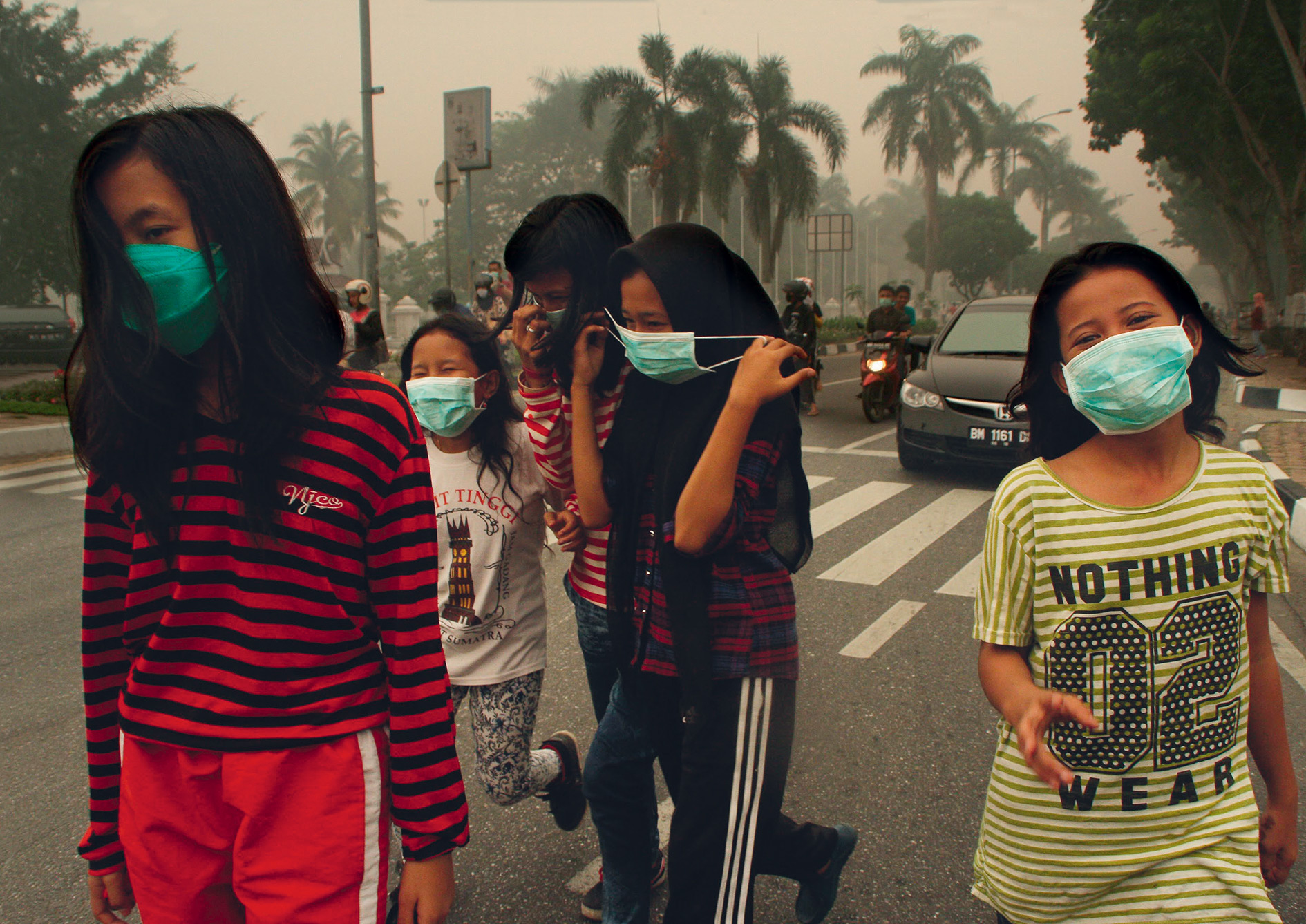 Young girls protect themselves from thick smoke as forest fires swept across Sumatra and Borneo in September 2015. The fires are set to clear the jungle to plant oil palms.