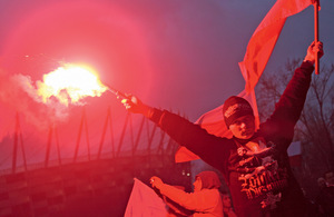 A young Pole wearing clothes with nationalistic symbols burns a flare in front of the National Stadium in Warsaw during the anti-migrant March of Independence in November 2015.Photo: Dominik Sipiński