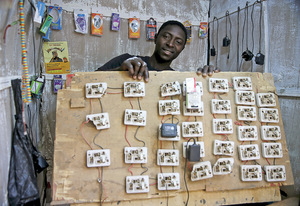 Charge your phones here: this man displays the board of sockets which helps him earn his livelihood in Nigeria's Katsina city. Many vendors invest in small solar units to generate the power.Photo: Akintunde Akinleye/Reuters