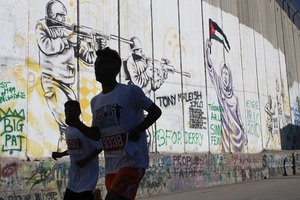 Running past Israel's Apartheid Wall, which separates Bethlehem from Jerusalem and people from their lands.Photo © Giedre Steikunaite