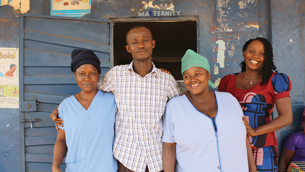 On high alert, post-Ebola: Nafisatu Jabbi (centre right) at the Koindu community clinic, accompanied by a newly replenished staff team, including Community Health Officer Alfonsus Vandi (centre left). Photo: Hazel Healy
