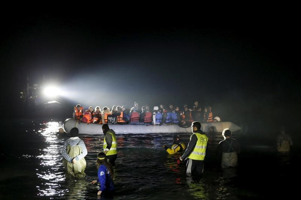 A rescue boat (L) shines a light on a dinghy carrying refugees and migrants as it approaches the shore near the city of Mytilene on the Greek island of Lesbos, March 20, 2016.