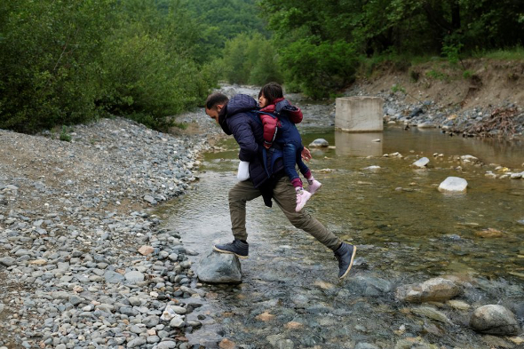 A man carrying a child who tried to cross the Greek-Macedonian border crosses a small river on their way back to a makeshift camp for refugees and migrants at the border near the village of Idomeni, Greece, May 12, 2016.