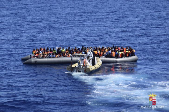 Migrants sit in their boat during a rescue operation by Italian Navy vessels off the coast of Sicily in this April 11, 2016 handout picture provided by Italy's Marina Militare.