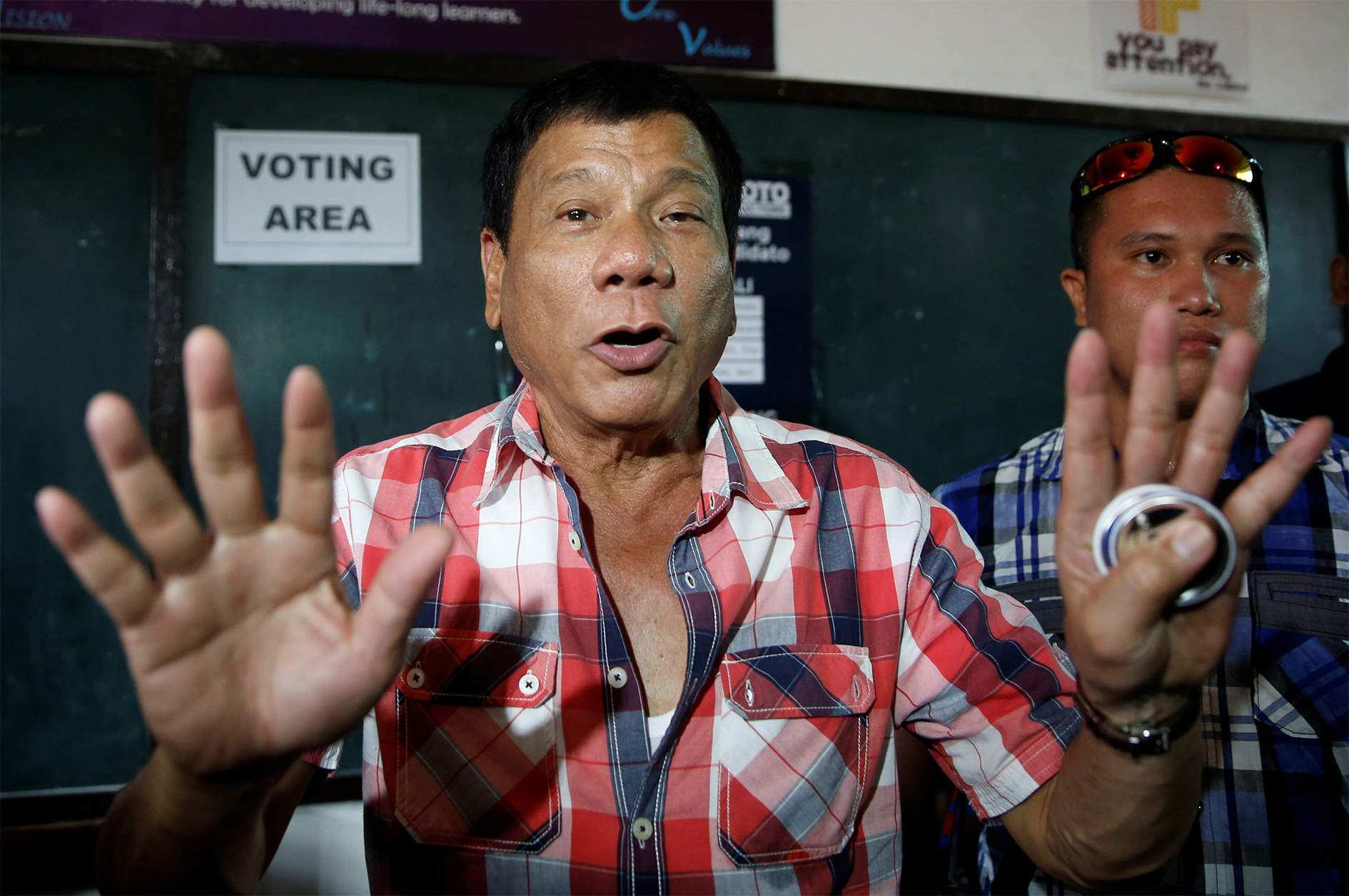 Presidential candidate Rodrigo 'Digong' Duterte talks to the media before casting his vote at a polling precinct for national elections at Daniel Aguinaldo National High School in Davao city in southern Philippines, 9 May 2016.
