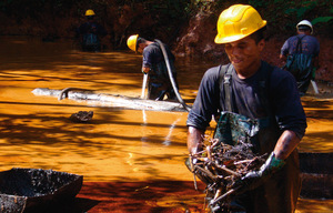 Dirty and dangerous – workers who clean up oil spills often suffer neurological and digestive problems. Cancer rates are higher in areas close to oil activity than in the rest of Ecuador. Photo: yasunigreengold.org / Oscar Francino / Ali Supay