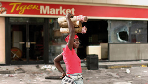 Riot act: a Haitian street vendor surveys the damage after food riots in Port-au-Prince, April 2008. Photo: Eduardo Munoz / Reuters