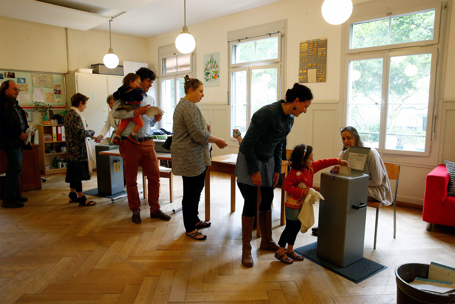 People cast their ballots during a vote on whether to give every adult citizen a basic guaranteed monthly income of 2,500 Swiss francs ($2,560), in a school in Bern, Switzerland, June 5, 2016.
