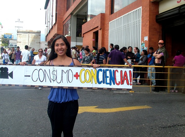 'Less consumerism, more consciousness' reads the placard of a young protestor outside a supermarket queue.