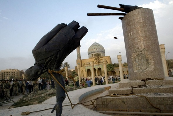 A statue of Iraq's President Saddam Hussein falls in central Baghdad 9 April 2003.
