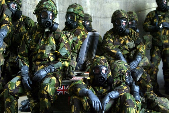 British Royal Air Force personnel wait in a bunker wearing full Nuclear Biological and Chemical suits after a warning of a Scud missile attack on their base in Kuwait 20 March 2003.