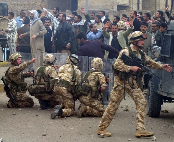 British Army troops take position near a crowd of protesting former Iraqi soldiers after stones were thrown in the southern Iraq city of Basra 6 January 2004.