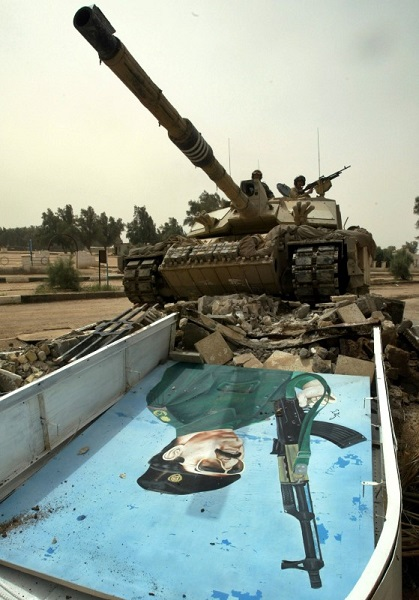 A British Army Challenger II tank crushes a portrait of Iraqi President Saddam Hussein at a former military training ground outside the southern city of Basra 27 March 2003. REUTERS/Chris Helgren/File Photo
