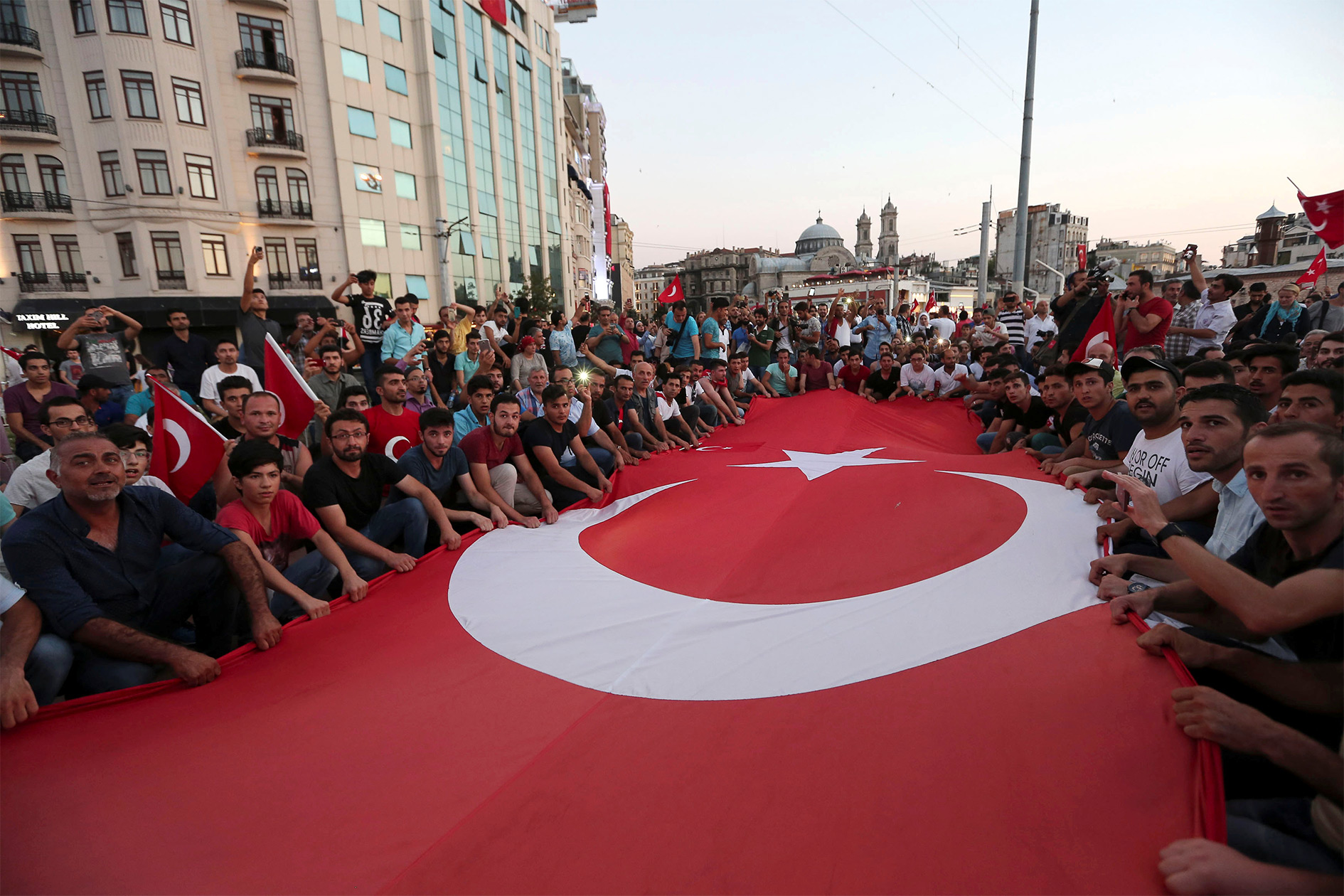 Supporters of Turkish President Tayyip Erdoğan wave a huge national flag as they gather at Taksim Square in central Istanbul, Turkey, 16 July 2016.