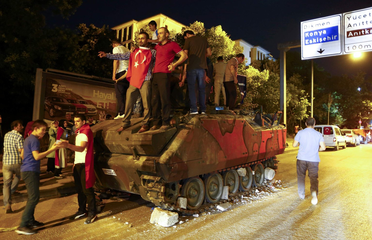 Supporters of Turkish President Tayyip Erdoğan stand on an abandoned tank during a demonstration outside parliament building in Ankara, Turkey, 16 July 2016.