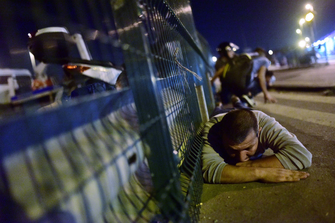 People take cover near a bridge during an attempted coup in Istanbul, Turkey.