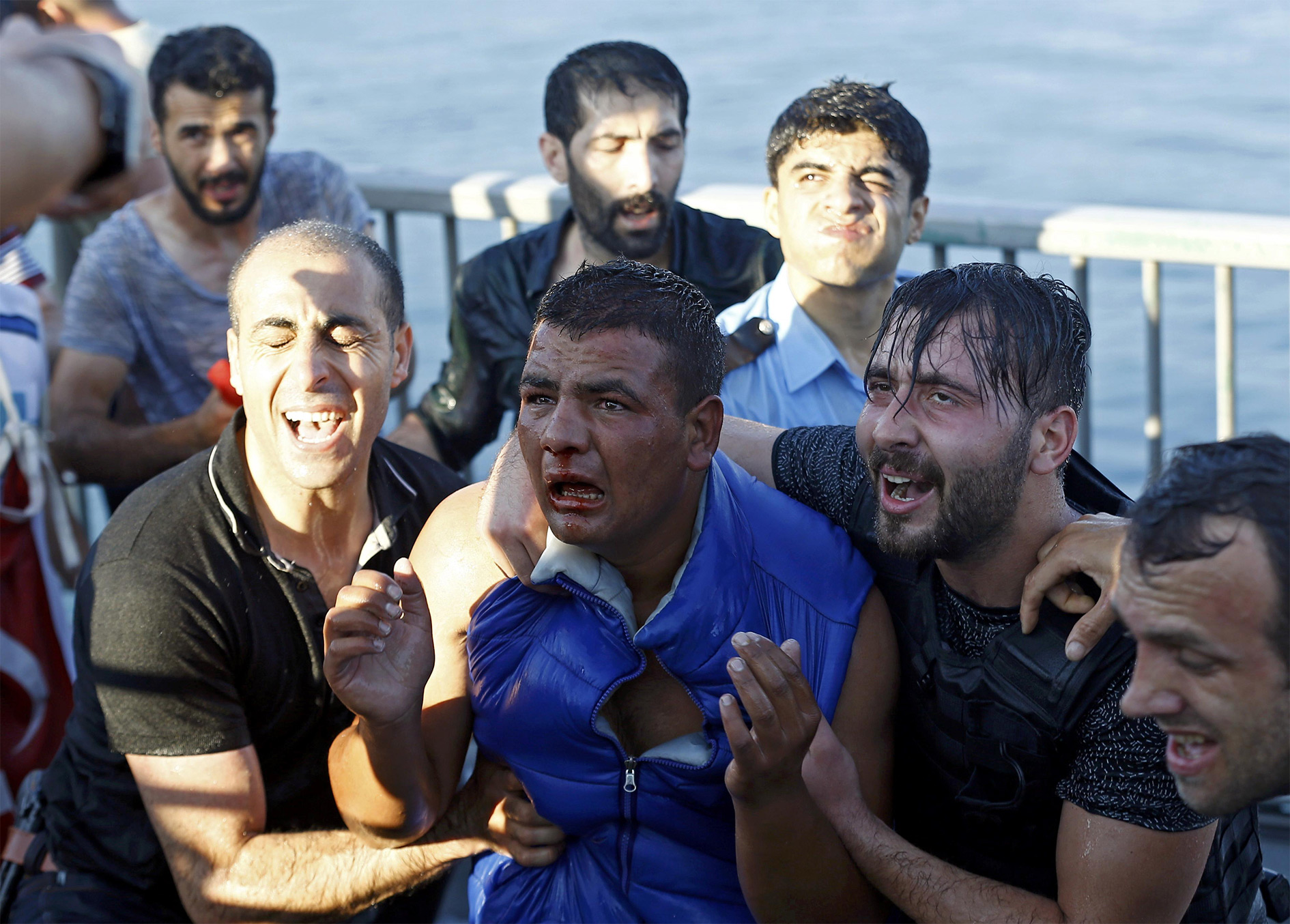 A soldier beaten by the mob (C) is protected by plain clothes policemen after troops involved in the coup surrendered on the Bosphorus Bridge in Istanbul, Turkey 16 July 2016.