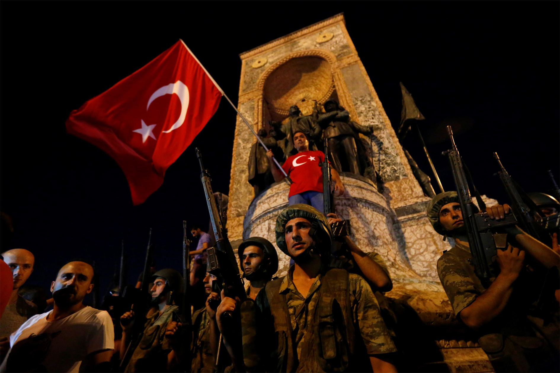 Turkish military stand guard near the Taksim Square as people wave with Turkish flags in Istanbul, Turkey, 16 July 2016.
